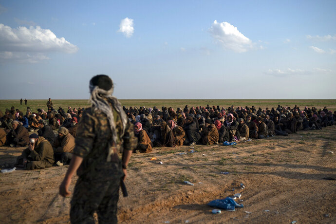 FILE - In this Feb. 22, 2019 file photo, U.S.-backed Syrian Democratic Forces (SDF) fighters stand guard next to men waiting to be screened after being evacuated out of the last territory held by Islamic State group militants, near Baghouz, eastern Syria. The SDF fighters who drove the Islamic State from its last strongholds called Monday, March 25, 2019, for an international tribunal to prosecute hundreds of foreigners rounded up in the nearly five-year campaign against the extremist group. (AP Photo/Felipe Dana, File)