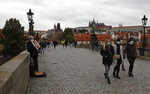 People walk across the medieval Charles Bridge in Prague, Czech Republic, Sunday, Oct. 11, 2020. The Czech Republic and neighboring Slovakia have registered big increases in coronavirus infections, setting a record for the fourth straight day. The government has responded to the record surge by imposing a series of new restrictive measures. Prime Minister Andrej Babis said on Friday he cannot rule out a lockdown of the entire country.  (AP Photo/Petr David Josek)