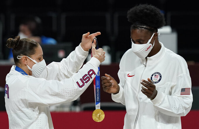United States's Diana Taurasi, left, puts a medal on teammate Sylvia Fowles during the medal ceremony for women's basketball at the 2020 Summer Olympics, Sunday, Aug. 8, 2021, in Saitama, Japan. (AP Photo/Charlie Neibergall)