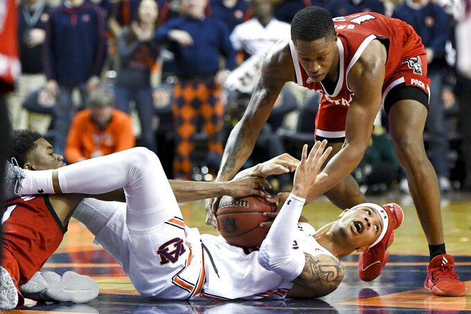 Auburn guard Samir Doughty (10) calls timeout during a struggle with North Carolina State guard Markell Johnson (11) and North Carolina State guard C.J. Bryce (13) for the ball during the second half of an NCAA college basketball game Thursday, Dec. 19, 2019, in Auburn, Ala. (AP Photo/Julie Bennett)