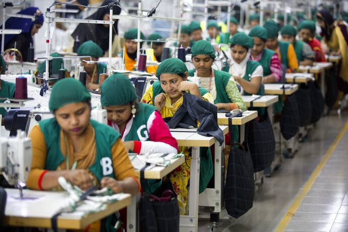 FILE - In this April 19, 2018 file photo, trainees work at Snowtex garment factory in Dhamrai, near Dhaka, Bangladesh. After months of decline in exports of its garment products, Bangladesh's economy is showing signs of recovery. The Asian Development Bank in a new report said Tuesday, Sept. 15, 2020, the country's economy's comeback was encouraging and it is expected to grow by 6.8 percent in the current fiscal year ending in June if this recovery sustains. (AP Photo/A.M. Ahad, File)