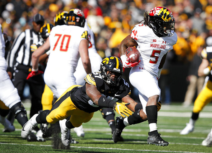 Maryland running back Anthony McFarland (5) is tackled by Iowa defensive end Chauncey Golston (57) during the second half of an NCAA college football game, Saturday, Oct. 20, 2018, in Iowa City, Iowa. Iowa won 23-0. (AP Photo/Charlie Neibergall)