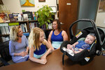 Megan Sims, second from right, along with daughter Aaliyah and son Christian, talks with Hendrée Jones, executive director of Horizons in Carrboro, N.C., Tuesday, July 13, 2021. Sims couldn't stop using drugs during the pandemic, even as she discovered she was pregnant. Through word of mouth, Sims discovered Horizons, a substance use disorder treatment program at the University of North Carolina's School of Medicine that is designed specifically for pregnant women and mothers. (AP Photo/Gerry Broome)