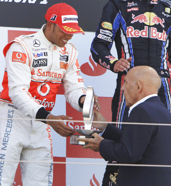 FILE - In this file photo dated Sunday, July 11, 2010, McLaren Formula One driver Lewis Hamilton, left, receives his trophy for second place from legendary British racing driver Stirling Moss at the British Formula One Grand Prix in Silverstone, England. Stirling Moss has died at the age of 90, according to an announcement Sunday April 12, 2020, from his family. (AP Photo/Mark Baker, FILE)