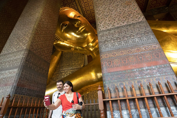 In this Feb. 7, 2020, photo, tourists take a selfie with the statue of a giant Buddha at Wat Pho in Bangkok, Thailand. There were less crowds in Bangkok's popular Wat Pho, a centuries-old Buddhist temple known for its giant reclining buddha, due to the virus scare. The complex of temples is normally visited by thousands of tourists. (AP Photo/Sakchai Lalit)