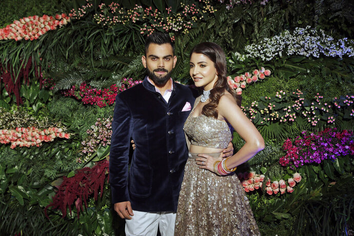 "FILE- In this Dec. 26, 2017 file photo, Indian cricketer Virat Kohli, left, and Bollywood actress Anushka Sharma, pose for the photographers during their wedding reception in Mumbai, India. Anushka Sharma has given birth to a baby girl, her husband and captain of the country's men's national cricket team, Virat Kohli, said Monday, declaring that the couple was beyond blessed to start ""this new chapter of our lives.""  (AP Photo/Rajanish Kakade, File)"
