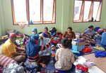 People who are displaced by floods sift through donated clothings at a temporary shelter in East Lewoleba, on Lembata Island, East Nusa Tenggara province, Indonesia, Tuesday, April 6, 2021. Multiple disasters caused by torrential rains in eastern Indonesia and neighboring East Timor have left a number of people dead or missing as rescuers were hampered by damaged bridges and roads and a lack of heavy equipment. (AP Photo/Ricko Wawo)