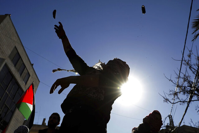 Protesters throw stone during a protest is held against the proposed peace deal for the Middle East by President Donald Trump, near the U.S. embassy in Aukar, east of Beirut, Lebanon, Sunday, Feb. 2, 2020. Hundreds of Lebanese and Palestinians demonstrated Sunday near the U.S. embassy in Lebanon in rejection to a White House plan for ending the Israeli-Palestinian conflict. (AP Photo/Hassan Ammar)