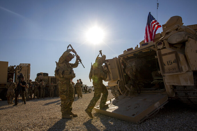 Crewmen enter Bradley fighting vehicles at a US military base at an undisclosed location in Northeastern Syria, Monday, Nov. 11, 2019. The deployment of the mechanized force comes after US troops withdrew from northeastern Syria, making way for a Turkish offensive that began last month. (AP Photo/Darko Bandic)