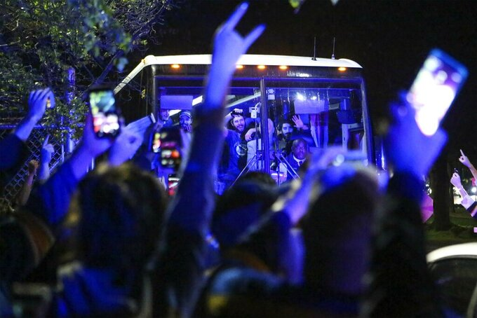 Fans gesture to members of the St. Louis Blues NHL hockey team after they boarded a bus at the airport in St. Louis early Thursday, June 13, 2019. The Blues defeated the Boston Bruins 4-1 in Game 7 of the Stanley Cup finals to win their first NHL championship Wednesday night in Boston. (Colter Peterson/St. Louis Post-Dispatch via AP)