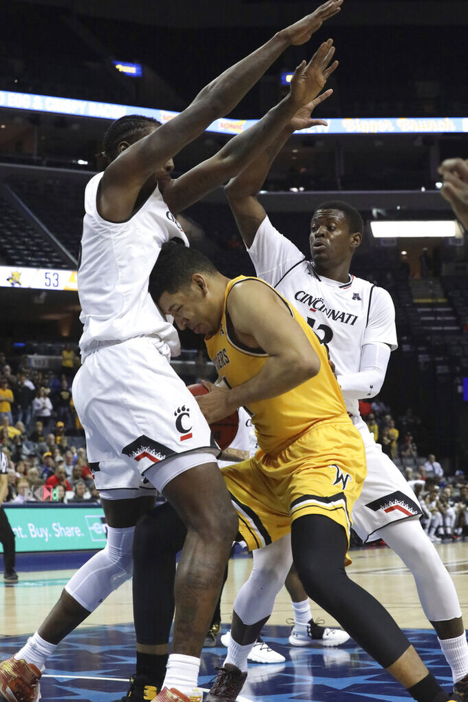 Wichita State's Jaime Echenique finds himself tightly guarded by Cincinnati's Nyster Brooks and Tre Scott in the second half of an NCAA college basketball game at the American Athletic Conference tournament Saturday, March 16, 2019, in Memphis, Tenn. (AP Photo/Troy Glasgow)