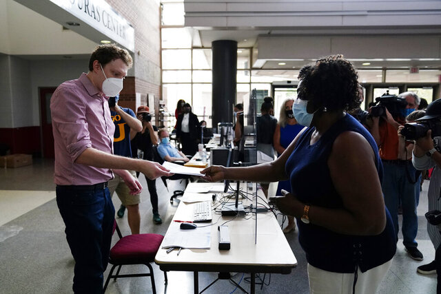 Philadelphia resident Priscilla Bennett receives her mail-in ballot at the opening of a satellite election office at Temple University's Liacouras Center, on Sept. 29, 2020, in Philadelphia.  Pennsylvania is one of this year's most hotly contested battleground states and also is facing a flurry of lawsuits, complaints and partisan finger-pointing over its election procedures and systems. (AP Photo/Matt Slocum)