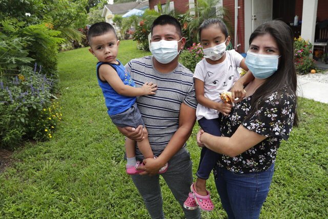 In this Sunday, June 7, 2020, photo, Elbin Sales, second from left, poses for a photograph with his wife, Yecenia Solorzano, right, and children Jordi Sales, left, and Athena Sales, amid the new coronavirus pandemic in Immokalee, Fla. Sales, who works as a landscaper, tested positive for COVID-19 and is quarantined at home with his family. Even as the pace of new cases has moderated in the state of Florida, this poor farmworking town in rural Florida is in the throes of an outbreak. (AP Photo/Lynne Sladky)