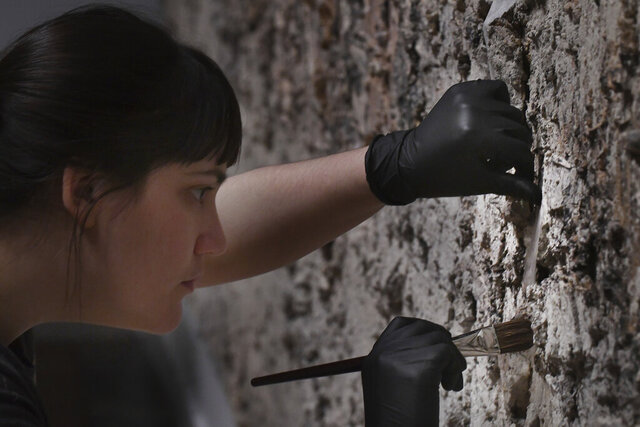 Detroit Institute of Arts Project Conservator Becca Goodman prepares the painting Das Geviert, 1997, by Anselm Kiefer to be removed from the wall where it has been since 2004, for an upcoming exhibition at the Detroit Institute of Arts in Detroit, Michigan on January 3, 2020. (Daniel Mears/Detroit News via AP)