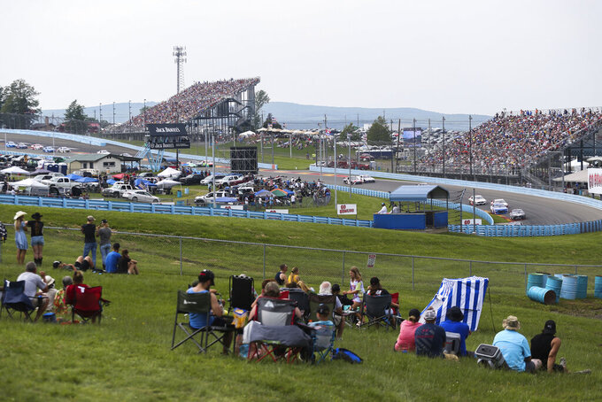 Spectators watch as cars turn into the esses during a NASCAR Cup Series auto race in Watkins Glen, N.Y., on Sunday, Aug. 8, 2021. (AP Photo/Joshua Bessex)