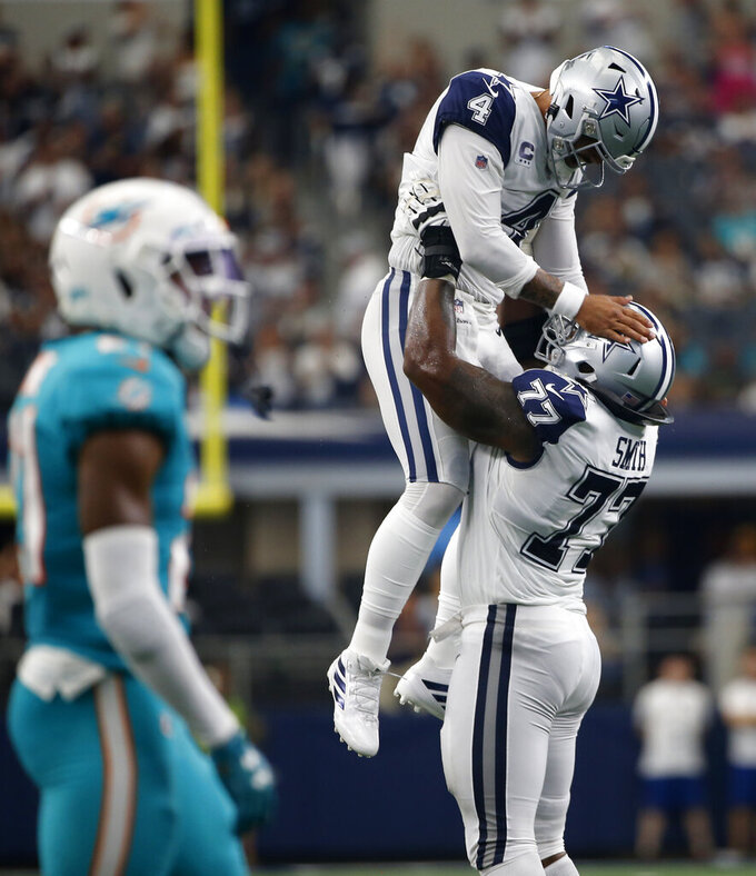 Dallas Cowboys quarterback Dak Prescott (4) is lifted by offensive tackle Tyron Smith (77) after throwing a touchdown pass to wide receiver Amari Cooper (not shown) in the second half of a NFL football game against the Miami Dolphins in Arlington, Texas, Sunday, Sept. 22, 2019. (AP Photo/Ron Jenkins)