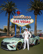 "In this image provided by Ethel M Chocolates, NASCAR driver Kyle Busch poses in front of the famous ""Welcome to Fabulous Las Vegas"" sign with his Ethel M Chocolates sponsor race car in Las Vegas. Busch first went to the Ethel M candy factory with his grandmother. It wasn't a tourist stop to the young Busch, it was a candy store and his grandmother let him roam the cactus garden and rewarded him with the craft chocolates. Ethel M is part of the Mars Corp., the longtime sponsor of Busch's team. Busch will feature the brand on his car in Sunday's race. (Christian Andrade-Cashman/Ethel M Chocolates via AP)"