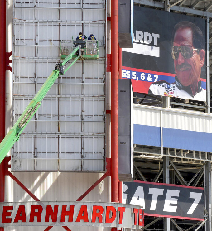 With a banner of former NASCAR driver Dale Earnhardt at upper right, workers perform maintenance on the illuminated signage on the Tower E elevator, Monday, April 1, 2019, in Bristol, Tenn. A full schedule of racing is coming up this weekend with the Bush's Beans Pole Day on Friday, the Alsco Xfinity Race 300 on Saturday, and the Monster Energy NASCAR Cup Food City 500 on Sunday. (David Crigger/Bristol Herald Courier via AP)