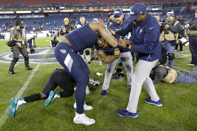 Tennessee Titans running back Derrick Henry gets help taking his jersey and shoulder pads off so he can trade jerseys with Jacksonville Jaguars running back Leonard Fournette after an NFL football game Sunday, Nov. 24, 2019, in Nashville, Tenn. The Titans won 42-20. (AP Photo/James Kenney)