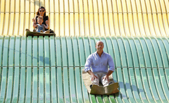Rep. John Delaney, D-Md., rides down the giant slide during a visit to the Iowa State Fair, Friday, Aug. 10, 2018, in Des Moines, Iowa. (AP Photo/Charlie Neibergall)
