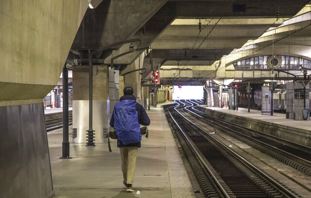 A raveler walks on a empty platform at at Gare Montparnasse train station during the 29th day of transport strikes in Paris, Thursday, Jan. 2, 2020. The start of 2020 was the second New Year celebration in a row where Macron has faced social upheaval. (AP Photo/Michel Euler)