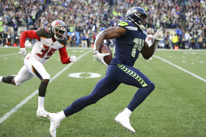 FILE - Seattle Seahawks wide receiver DK Metcalf, right, runs to score a touchdown ahead of Tampa Bay Buccaneers defensive back Jamel Dean during the second half of an NFL football game in Seattle, in this Sunday, Nov. 3, 2019, file photo.  Seahawks wide receiver DK Metcalf is explosive off the line of scrimmage. But Sunday, May 9, 2021, he will venture into a new sort of lane to test his speed on a different sort of line, one that's filled with Olympic-caliber sprinters. (AP Photo/Scott Eklund, File)