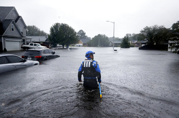 FILE - In this Sunday, Sept. 16, 2018 file photo, a member of the North Carolina Task Force urban search and rescue team wades through a flooded neighborhood looking for residents who stayed behind as Florence continues to dump heavy rain in Fayetteville, N.C. According to data released by the National Oceanic and Atmospheric Administration on Tuesday, May 4, 2021, the new United States normal is not just hotter, but wetter in the eastern and central parts of the nation and considerably drier in the West than just a decade earlier. (AP Photo/David Goldman)
