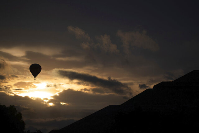 A hot air balloon flies tourists near the Pyramid of the Sun in Teotihuacan, Mexico, Thursday, Sept. 10, 2020. After closing for five months due to the restrictions imposed by the COVID-19 pandemic,