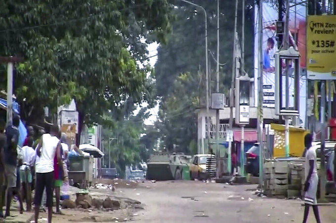 In this image made from video, residents watch as an armored personnel carrier is seen on the streets near the presidential palace in the capital Conakry, Guinea Sunday, Sept. 5, 2021. Mutinous soldiers detained President Alpha Conde on Sunday after hours of heavy gunfire rang out near the presidential palace, then announced on state television that the government had been dissolved in an apparent coup d'etat. (AP Photo)