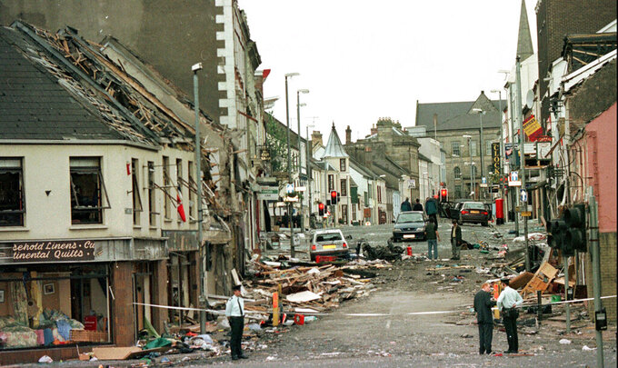"""FILE - This is a Saturday, Aug. 15, 1998 file photo shows Royal Ulster Constabulary Police officers standing on Market Street, the scene of a car bombing in the centre of Omagh, Co Tyrone, 72 miles west of Belfast, Northern Ireland.  A judge in Northern Ireland says there is plausible evidence that authorities could have prevented the worst single atrocity of the Troubles. High Court Justice Mark Horner recommend Friday, July 23, 2021 that authorities in the U.K. and the Republic of Ireland open an investigation into the Omagh bombing that killed 29 people. Horner says that an investigation was necessary to determine whether a more """"proactive"""" security approach might have thwarted the attack on Aug. 15, 1998. (AP Photo/Paul McErlane, File)"""