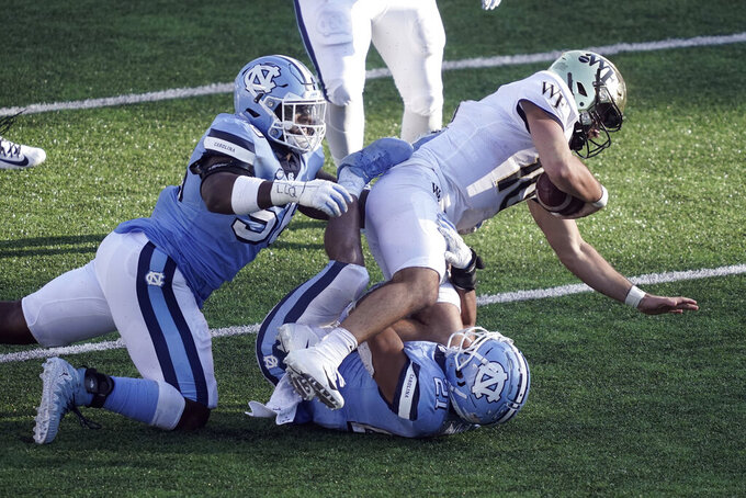 North Carolina defensive lineman Tomari Fox (56) and linebacker Chazz Surratt (21) tackle Wake Forest quarterback Sam Hartman (10) during the second half of an NCAA college football game in Chapel Hill, N.C., Saturday, Nov. 14, 2020. (AP Photo/Gerry Broome)