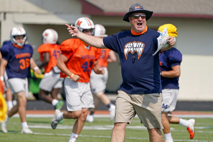 Midland University head coach Jeff Jamrog calls a play during NAIA college football practice in Fremont, Neb., Tuesday, Aug. 25, 2020. Midland University is among five small colleges in the state that are pushing forward with plans to play football this fall. The Nebraska Cornhuskers, meanwhile, won't play after Big Ten presidents voted to move back football season until after Jan. 1. (AP Photo/Nati Harnik)