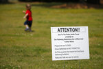 A child plays near a sign advising people that the playground is closed and social distancing is requirements Thursday, April 9, 2020, in Rutledge, Ga. The new coronavirus causes mild or moderate symptoms for most people, but for some, especially older adults and people with existing health problems,  it can cause more severe illness or death.(AP Photo/John Bazemore)
