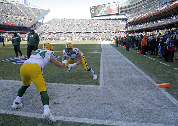 In this Dec. 16, 2018 photo, Green Bay Packers defensive end Dean Lowry (94) and defensive tackle Tyler Lancaster (95) warm up as fans watch from the sideline before an NFL football game against the Chicago Bears in Chicago. The Bears have ended a pregame perk that prompted a lawsuit by a lifelong Green Bay Packers fan who wanted to wear the Wisconsin team's green and gold apparel to warmups at Soldier Field. Bears attorney Paul Greenwalt tells The Chicago Tribune that the team is eliminating the program that allows season ticket holders to attend pregame warmups in a marketing reorganization. (AP Photo/David Banks)
