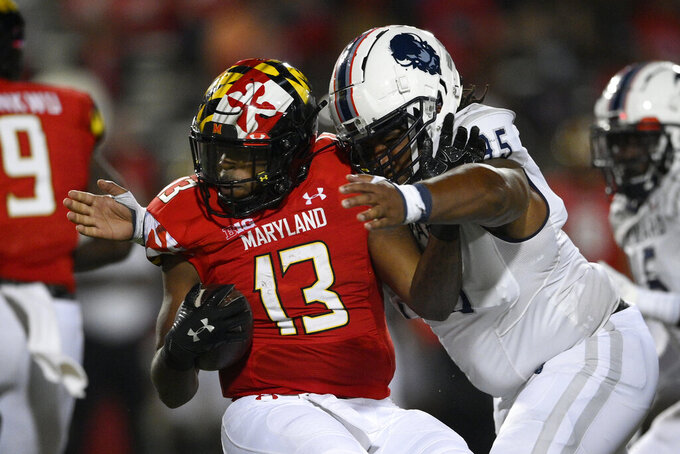 Howard defensive lineman James Gore, front right, tackles Maryland running back Peny Boone (13) during the first half of an NCAA college football game, Saturday, Sept. 11, 2021, in College Park, Md. (AP Photo/Nick Wass)