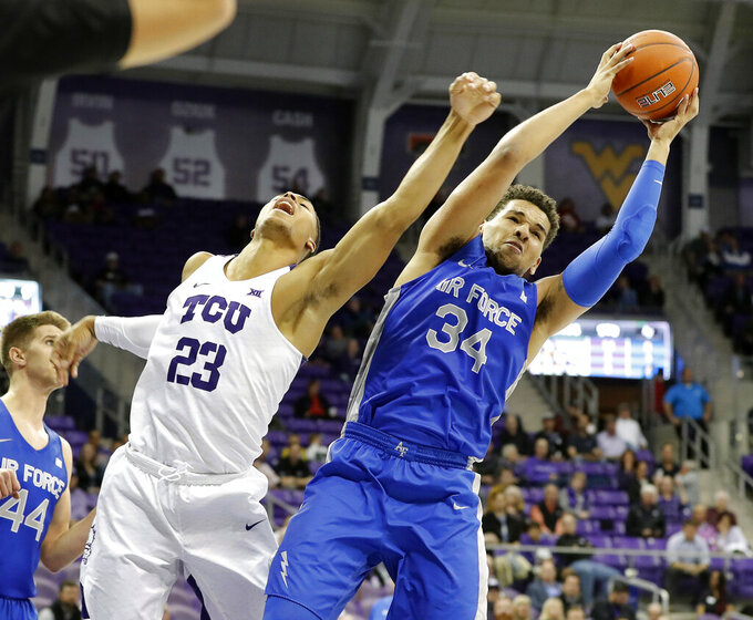 Air Force center Ryan Swan (34) grabs a rebound from TCU guard Jaedon Ledee (23) in the first half of an NCAA college basketball game in Fort Worth, Texas, Monday, Nov. 18, 2019. (Bob Booth/Star-Telegram via AP)