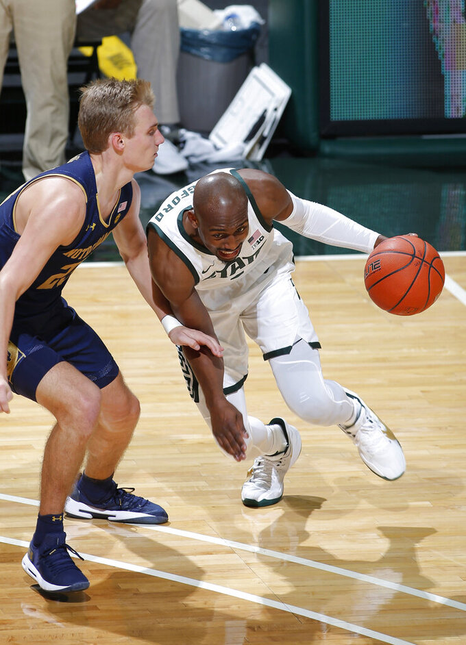 Michigan State's Joshua Langford, right, drives against Notre Dame's Dane Goodwin during the second half of an NCAA college basketball game Saturday, Nov. 28, 2020, in East Lansing, Mich. Michigan State won 80-70. (AP Photo/Al Goldis)