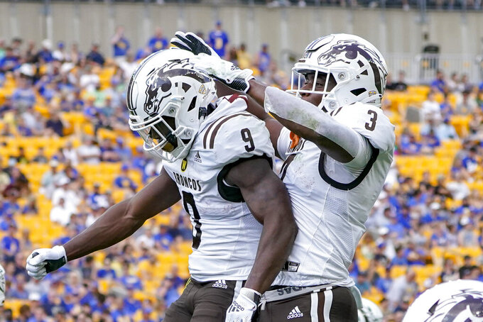 Western Michigan running back Sean Tyler (9) celebrates with La'Darius Jefferson (3) after scoring a touchdown against Pittsburgh during the first half of an NCAA college football game, Saturday, Sept. 18, 2021, in Pittsburgh. (AP Photo/Keith Srakocic)