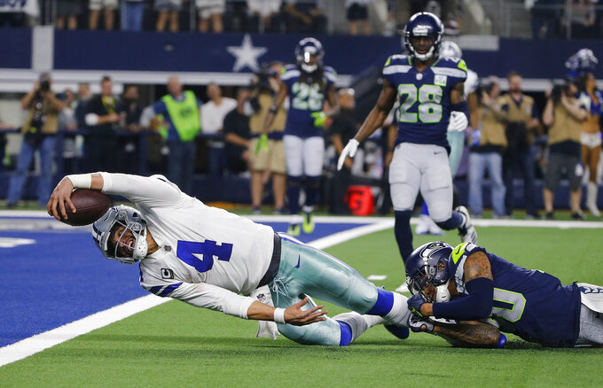 Dallas Cowboys quarterback Dak Prescott (4) advances the ball to the 1-yard line on a short run for the end zone as Seattle Seahawks safety Bradley McDougald (30) makes the stop during the second half of the NFC wild-card NFL football game in Arlington, Texas, Saturday, Jan. 5, 2019. (AP Photo/Michael Ainsworth)