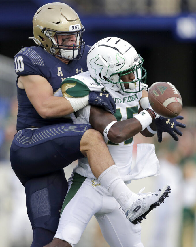 Navy safety Kevin Brennan, left, breaks up a pass intended for South Florida wide receiver Jernard Phillips during the first half of an NCAA college football game, Saturday, Oct. 19, 2019, in Annapolis. (AP Photo/Julio Cortez)