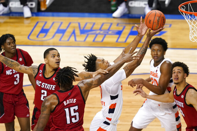 Syracuse forward Alan Griffin, center, takes a shot as North Carolina State guard Shakeel Moore (2) and forward Manny Bates (15) defend during the second half of an NCAA college basketball game in the second round of the Atlantic Coast Conference tournament in Greensboro, N.C., Wednesday, March 10, 2021. (AP Photo/Gerry Broome)