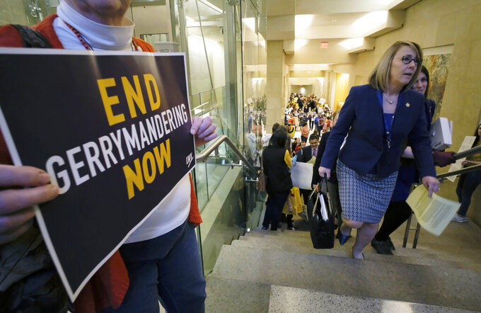 """FILE - In this March 2, 2020, file photo, Del. Martha Mugler, D-Hampton, second from right, and Del. Danica Roem, D-Prince William, right, walk past a group of demonstrators as they head to the House of Delegates inside the Virginia state Capitol in Richmond, Va. Democrats are wondering if they erred in pushing too hard in some states for a nonpartisan redistricting process. Redistricting is the once-a-decade process by which state legislatures redraw political maps. Parties can gain major advantages if they draw seats in a way that favors their candidates. But Democrats have partly turned against this process, known as """"gerrymandering."""" (Bob Brown/Richmond Times-Dispatch via AP)"""