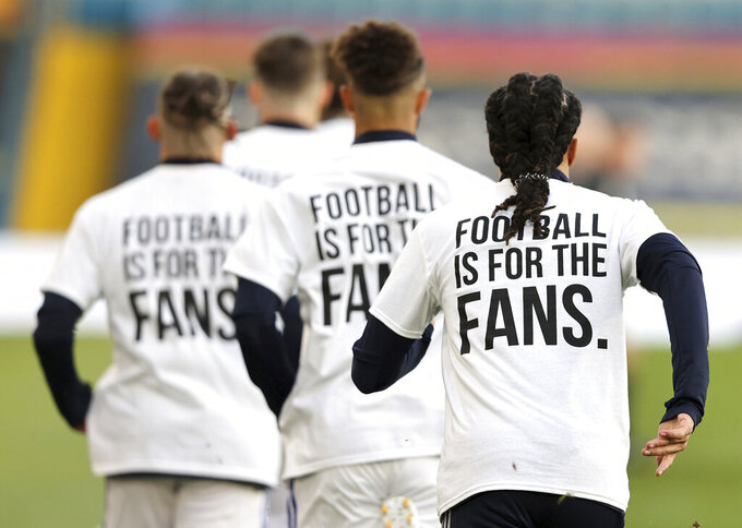 Leeds United players wear t-shirts with the logo 'Football Is For The Fans' as they warm-up ahead of ahead of the English Premier League soccer match between Leeds United and Liverpool at the Elland Road stadium in Leeds, England, Monday, April 19, 2021. (Clive Brunskill/Pool via AP)