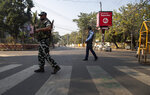 A paramilitary soldier walks over a zebra line on which is written 'No CAB' during a shutdown protest against the Citizenship Amendment Bill (CAB) in Gauhati, India, Tuesday, Dec. 10, 2019. Opponents of legislation that would grant Indian citizenship to non-Muslim illegal migrants from Pakistan, Bangladesh and Afghanistan have enforced an 11-hour shutdown across India's northeastern region. (AP Photo/Anupam Nath)