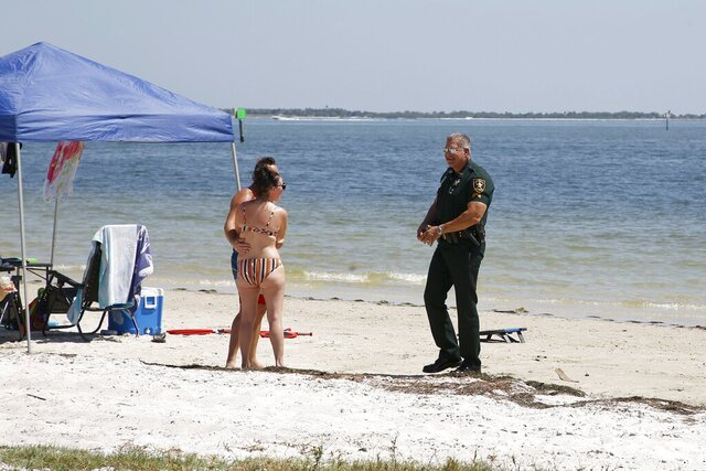 Pinellas County Sheriff, Sgt. Bryan Bingham talks with a couple reminding them of social distancing from others not in their household. Despite warnings and roadblocks dozens of vehicles made their way onto the Pinellas County side of Gandy blvd. at the unofficial Gandy Beach on the first weekend of the safer at home order on Sunday, March 29, 2020 in St. Petersburg, Florida. Deputies at one time responded to the area to remind citizens to keep their distance from others and avoid gathering in groups. (Luis Santana/Tampa Bay Times via AP)