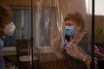 In this Monday, June 22, 2020 photo and in their first encounter in more than 100 days due to restrictions to fight the coronavirus pandemic, Isabel Pérez López, 96, reacts before receiving an embrace through a plastic film screen from her visiting daughter, Beatriz Segura, 67 at a nursing home in Barcelona, Spain. (AP Photo/Emilio Morenatti)