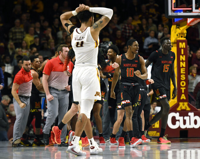 Minnesota guard Payton Willis, foreground, walks off the court as Maryland's Serrel Smith Jr. (10) and Chol Marial (15) celebrate Maryland's 74-73 win in an NCAA college basketball game Wednesday, Feb. 26, 2020, in Minneapolis (AP Photo/Hannah Foslien)