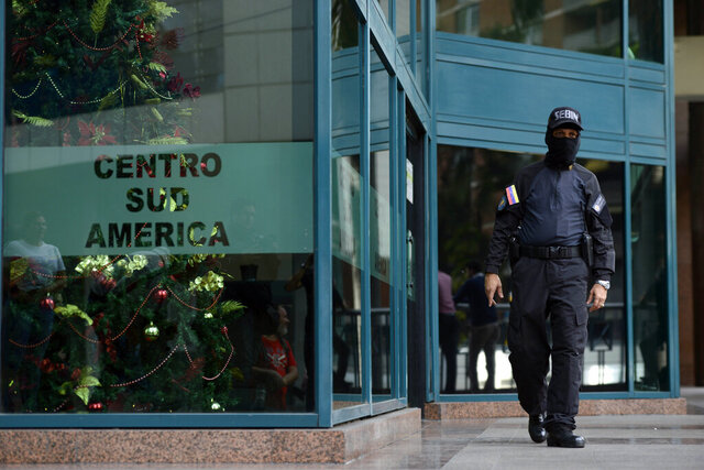 A Venezuelan security officer guards the entrance, after other officers entered the building where the offices of Venezuela's opposition leader Juan Guaido are located, in Caracas, Venezuela, Tuesday, Jan. 21, 2020. (AP Photo)