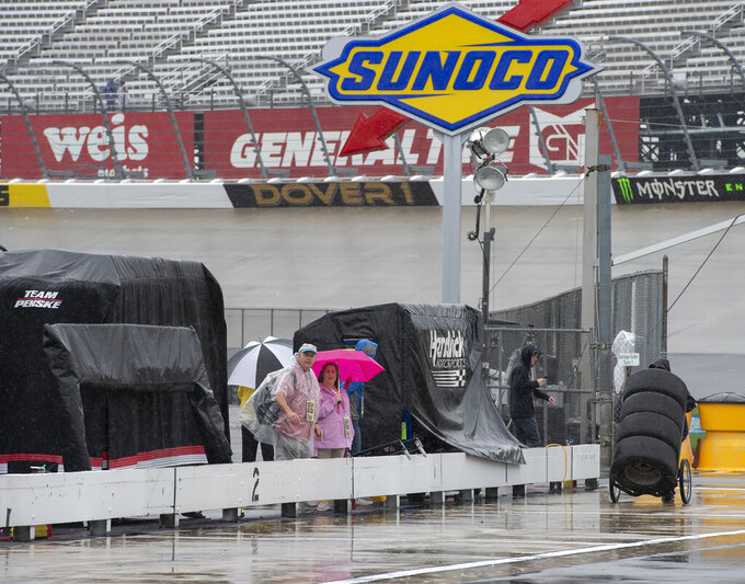 People wait in the rain before a NASCAR Cup series auto race at Dover International Speedway in Dover, Del., Sunday, May 5, 2019. (AP Photo/Jason Minto)