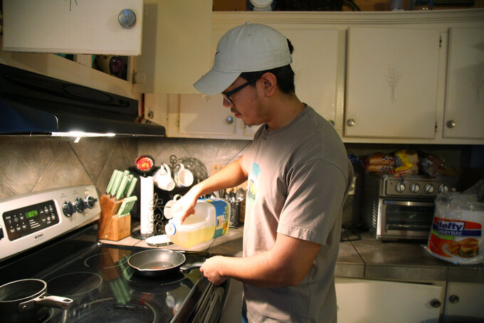 Samuel Alfaro, 19, starts to cook his breakfast at his home in Houston, Texas, Friday July 23, 2021. Alfaro said his appointment to obtain deferred action for childhood arrival or DACA immigration status was canceled due to a recent federal court ruling against the program. (AP Photo/John L. Mone)